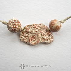 An organic stoneware pendant made from a mould created from a pyrite Ammonite fossil from the Jurassic coast of England and two coordinating beads.