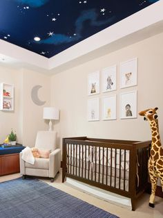 Simple framed prints of animals hang above the crib for a chic, minimalistic arrangement. The chocolate brown crib grounds this nursery with creamy white walls and an entrancing ceiling mural of the night sky. A life-sized stuffed giraffe is not only fun to play with, but adds a whimsical element to the room as well.