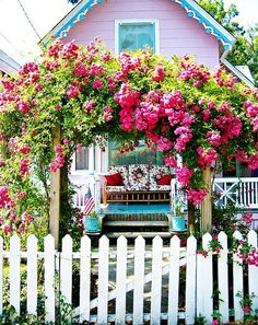 little pink house, white picket fence and a rose arbor! perfect! So sweet and cute! Maybe a place for Craig and I to retire to :)