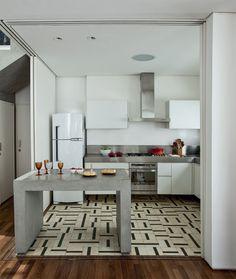 Cercada de portas de correr, a cozinha se integra à sala, com piso de ladrilhos hidráulicos