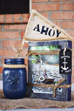 Distressed wood block picture frame with a painted glass mason jar tied with nautical rope and ahoy flag table display | Deegan's Nautical First Birthday Party | Deegan is one |