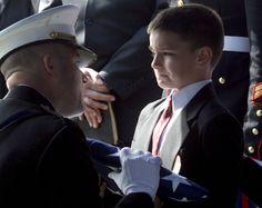 Christian Golczynski de oito anos recebe a bandeira pelo seu falecido pai, o Sargento da Marinha Marc Golczynski, durante a missa memorial.