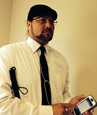 """""""Accessible iPhone Apps That Help Me Manage Work, Life, and Travel as a Blind Professional"""": Joe Strechay, CareerConnect program manager, writes about his favorite apps for keeping up with work, sports, restaurant options, reading, and more. (Image: Joe Strechay using his iPhone, with his cane tucked under his arm)"""