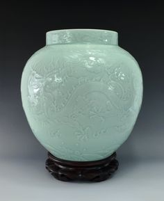 LARGE Fine Carved Dragon Jar. of Bulbous body, with shallow neck to the wide opening. The body decorated in delicate carving in shallow relief of an enormous imperial dragon chasing a flaming pearls amidst flames and clouds above lishui wavy water. Displayed on carved wooden stand. Mark on base, six blue seal script -ZhuanShu- character, QianLong Reign Period of Great Qing.