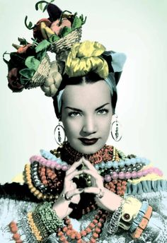 "Carmen Miranda, the stage name of Maria do Carmo Miranda da Cunha, moved to Brazil with her family when she was still a child. In 1925, as a sixteen year old in Rio de Janeiro, she discovered she had a talent for creating hats and dresses while working in a clothing shop. She began to design and sew her own costumes when in 1930 she started singing professionally. Her first real creation came when – standing just five foot tall – she was ""encouraged"" to wear platforms."