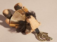 A Burberry charm featuring Thomas Bear, our signature teddy, in soft check cashmere with a metallic cape and shearling collar. This item is a collector's piece and is not suitable for children under 36 months.