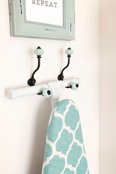 Colorful hooks that tie into colors on ironing board cover. DIY Laundry Room Storage Shelves Ideas (3)
