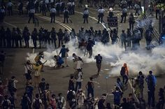 Umbrella Revolution Hong Kong, Demonstrators disperse as tear gas is fired by police during a protest on September 29, 2014 in Hong Kong. Thousands of people kicked off Occupy Central by taking over Connaught Road, one of the major highway in Hong Kong, in protest against Beijing's conservative framework for political reform. (Photo by Anthony Kwan/Getty Images)