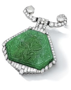 Art Deco Emerald and Diamond Brooch, Cartier, Circa 1925 Centring on a shield-shaped carved emerald, to the marquise-shaped, circular-cut and baguette diamond surround and surmount, decorated with carved colourless stones and black enamel, mounted in platinum, signed Cartier and numbered, with French assay marks.