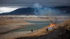 """""""State park rangers burned weeds on the Exposed lake bed of the Rye Patch Reservoir in Nevada, which was at 3.5 percent capacity amid a drought that has caused the worst water shortage the region has faced in more than a century."""" Max Whittaker for the New York Times"""