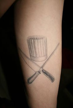 """A chef's hat above a crossing knife and sharpener. """"Arrgh! Here be the pirates of haute cuisine!"""""""