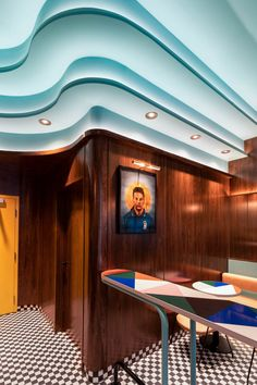 Continuing the cafe's curving lines, the ceiling's exaggerated cornicing is another retro visual element. As with the main bar and the checkerboard floor, the cornicing seamlessly blends the walls and the ceiling together.