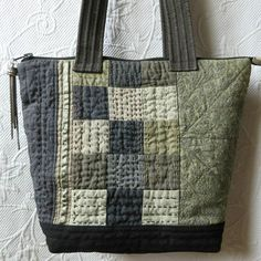 This unique quilted bag was made from repurposed linen, cotton, silk, and hemp fabrics in shades of grey, taupe, khaki and brown. Many hours of hand stitching with cotton perle embroidery thread on both sides add detail. I just love the textured effect that hand stitching gives the