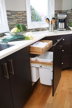 Kitchen Design Idea - Hide Pull Out Trash Bins In Your Cabinetry   The pull out trash bins in this kitchen hang but are lower down to accommodate a drawer that sits above them.