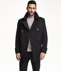 Double-breasted black pea coat in twill with wide notch lapels. Side pockets, two inner pockets, and tabs at cuffs. Vent at back. Lined. | H&M For Men