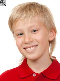 Mullet cut for young boys. Textured hair with a short front and longer strands in the back.
