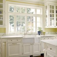 Sullivan Conard Architects - kitchens - white and yellow, white and yellow kitchen, yellow walls, yellow paint, pale yellow ceiling, apron sink, white porcelain apron sink, glass-front cabinets, glass-front upper cabinets, lined glass-front cabinets, white kitchen cabinets, raised panel cabinets, raised panel base cabinets, white raised panel cabinets, calcutta marble, calcutta marble countertops, kitchen hardwood floors, pot lights, recessed lighting,