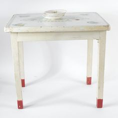 "A vintage enamel top child's Nursery Rhyme table with Warner Keffer saucers. The table features an enamel top with nursery rhyme graphics, has a wooden base painted white, four square legs with red painted feet. The saucers are 4.75"" in diameter and feature transferware design with figures, marked ""Warner Keffer, China Co., E. Liverpool"" in red on the underside."