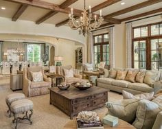 all-neutral living room in warm shades with shabby chic furniture and wooden beams on the ceiling