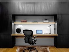 This home office is surrounded by black cabinetry, directly contrasting the…