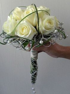 White roses bridal bouquet in an armature of silver decorative Oasis wire and lily grass accent