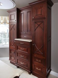 In keeping with the dark wood theme of the master bathroom design, this cabinet unit offers plenty of storage space for two. The custom piece spans one wall of the master bath from floor to ceiling and provides plenty of drawer and cabinet space in the center, with identical his and her cabinets and drawer space on each side. Designed by Susan Brunstrum.