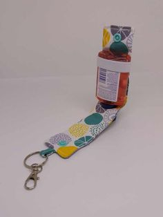 These handmade hand sanitiser holders are useful and can be clipped onto bags or belts. The bottle is held in place by elastic and closed with a snap fastener.