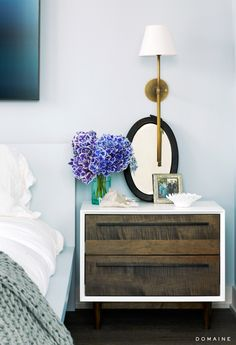 Bedside table styled with purple flowers and oval mirror