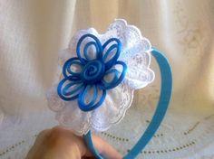Diadema forrada con cinta de raso, adornada con rosetón de tira bordada y terminada en el centro con una flor de cordón de raso en dos tonos de azul, se puede realizar en otros colores.