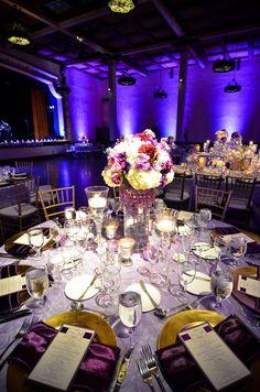 Blue-purple up lighting, white linen, gold charger, purple napkin....