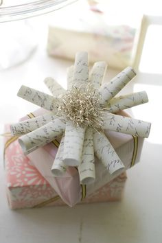 cute gift wrapping bow made out of old pages rolled into a tube and stapled. I might be tempted to print out old script just to make these!