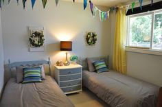Kids' room with mismatched painted wood headboards, strung pennants, floral wreaths, blue and white painted chest, cheery yellow curtains Painted Wood Headboard, Painted Chest, Yellow Curtains, Painting On Wood, Bird Houses, Kids Room, Blue And White, Floral Wreaths, Headboards