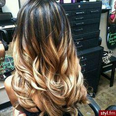 Dark black roots, warm caramel brown highlights to light blonde curls