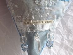 """CAROLYN SAXBY TEXTILES - icicles - a new ice blue winter heart with softly dyed fabrics, heat distressed chiffons, clear plastic and sparkly snowflakes. Backed with ice blue velour and finished with crystal icicle danglies. The text is """"when winter came"""" Carolyn Saxby, Ice Heart, Beast From The East, Pretty Beach, How To Make Tea, Textile Artists, Pattern Paper, Book Art, Two By Two"""