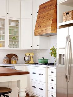 A+white+kitchen+demands+white+or+stainless+components+--+right?+Creative+remodeling+can+turn+that+on+its+head,+with+an+inventive+use+of+materials+that+adds+trend-forward+personalization+as+well+as+warmth+and+visual+interest.+This+distinctive+vent+hood,+crafted+from+rustic+wood,+picks+up+on+the+tones+of+the+island+and+floor,+even+as+it+adds+its+own+perfect+imperfections+to+the+room's+mix.