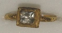 Gold ring, the high square and moulded bezel set with a pyramid-shaped crystal, the hoop engraved and enamelled on the shoulders