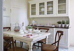 Cocina con mesa blanca y sillas marrones