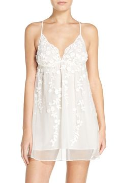 Embroidered appliqués blossom over this gauzy chemise in a charming babydoll silhouette.