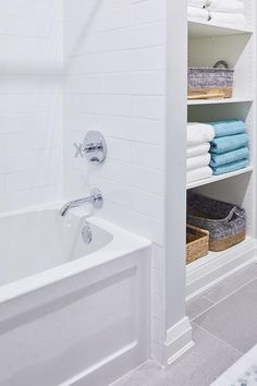 White modular shelves are mounted beside a drop-in bathtub fitted with white horizontal surround tiles and a polished nickel shower kit.