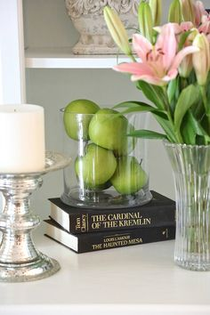 Faux green apples layered in a glass candleholder.