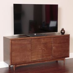 The Mid Century 66 wide console with sliding doors evokes the 'retro' fell and function of authentic Mid Century Modern styling in a beautiful walnut finish, with attention to detail at every point.