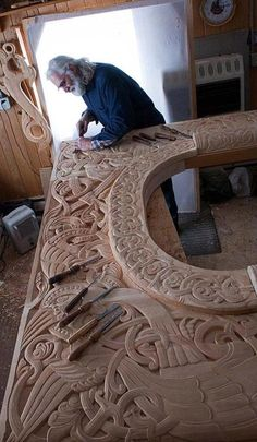 Craftsman at work. Looks like the upper section of a fireplace mantle. Just great and painstaking work.