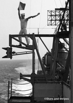 Mediterranean Sea, December, 1967: Even as computers and satellites were bringing about great advances in the U.S. Navy's communications systems, the old ways still had their place on the high seas. Here, a sailor braves the wind to signal other ships during 6th Fleet maneuvers in the Mediterranean. (Gus Schuettler ©Stars and Stripes)