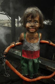 Manila, Philippines.  Children are employed for their small sizes and cheap salary. They could easily crawl into those small pits behind.  But the condition is really terrible. Hot, smoky, polluted and bad for health.