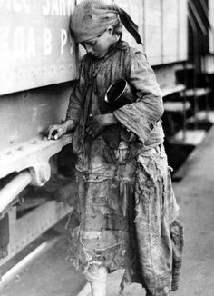 Famine in Russia (1921-1923): Young girl in rags at Saratov railway station, gathering precious grains of wheat
