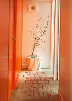 Dans ce couloir magique, tout de orange vêtu, les habitants ont eu la bonne idée de casse la longueur un peu ennuyeuse en dessinant une marelle sur le sol. Une fois atteint le « septième ciel », un tabouret blanc en tronc d'arbre de Home autour du monde soutient une lampe fleurs.