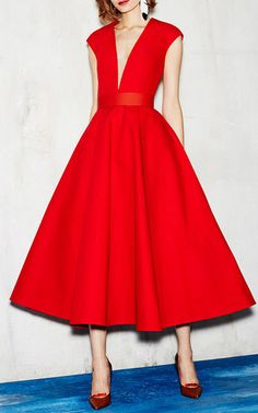 This **Paule Ka** dress features a plunging V-neckline and a full bodied pleated A-line midi skirt.