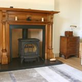 Victorian pillared oak fireplace with wood burning stove.