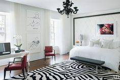 Suite master elegante e aconchegante em preto e branco, com tapete com listras de zebra, lustre preto e poltronas em couro vermelho.
