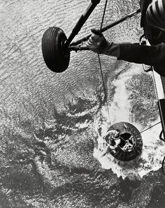 U.S. Marine helicopter recovery team hoists astronaut Alan Shepard from his Mercury spacecraft after a successful flight and splashdown in the Atlantic Ocean. On May 5th 1961, Alan B. Shepard Jr. became the first American to fly into space. His Freedom 7 Mercury capsule flew a suborbital trajectory lasting 15 minutes 22 seconds.